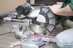 Elektryczny Zobaczył w pracownik rękach Kurenda zobaczył tnącego drewnianego promień zdjęcie stock
