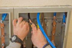 Elektryk łączy druty w elektrycznym gabinecie 2 Zdjęcie Stock