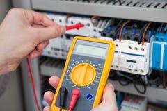 Elektryk egzamininuje fusebox z oporu testrem Zdjęcia Stock