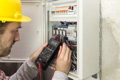 Elektryk przy pracą mierzy elektrycznego prąd fotografia royalty free