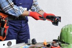 Elektryk przy pracą w bezpieczeństwie na mieszkaniowej instalaci elektrycznej Fotografia Stock