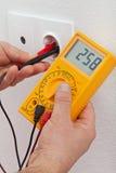 Elektryk wręcza pomiarowego woltaż w elektrycznym ujściu Zdjęcie Royalty Free