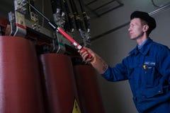 Elektryk wykonuje rutynowego utrzymanie na wysokim woltażu transformatorze zdjęcie royalty free