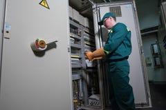 Elektryka inżynier jest probierczym elektrycznym wyposażeniem przy wielką rośliną fotografia stock