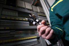 Elektryka inżynier jest probierczym elektrycznym wyposażeniem przy wielką rośliną zdjęcie royalty free