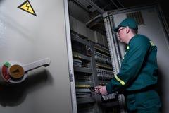 Elektryka inżynier jest probierczym elektrycznym wyposażeniem przy wielką rośliną zdjęcia royalty free