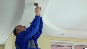 Elektryka mężczyzna bierze out fluorowa i sprawdza lampowa żarówka zbiory