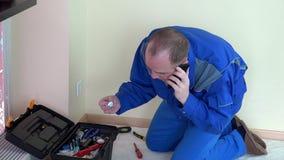 Elektryka mężczyzna rozmowa na telefonu komórkowego i wszywki zbawczej szpilce ujście zdjęcie wideo