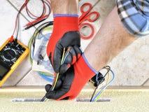 Elektryka technik przy pracą z zbawczym wyposażeniem na mieszkaniowej instalaci elektrycznej Fotografia Royalty Free