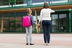 Elementär studentflicka med modern på skolgården arkivbild