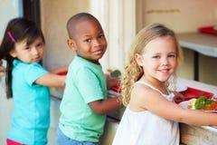 Elementära elever som samlar sund lunch i kafeteria Arkivfoton