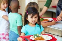Elementära elever som samlar sund lunch i kafeteria Arkivfoto