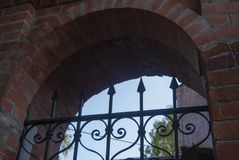 Element of ancient church architecture. An arch of red brick and openwork forged lattice Stock Photography