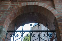Element of ancient church architecture. An arch of red brick and openwork forged lattice Royalty Free Stock Photo