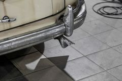 The element of the back of the body of the old Soviet retro car Chrome-plated gaz m20 bumper and exhaust pipe in a car repair royalty free stock photography
