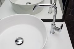 Element of bathroom interior with white sink and large mirror. New wash basin and black hexagonal tiles tile stock photos