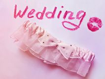 Element of a bride`s wedding dress. Wedding Garter. Element of a bride`s wedding dress. Beautiful bridal background in tender pink color with garter and word Royalty Free Stock Photo