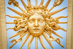 Element of golden gate of Chateau de Versailles. Detail view of golden ornate gate of Chateau de Versailles depicting human face. Blue sky in background. Paris royalty free stock images