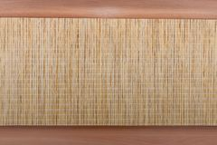 Element of interior decoration of the house. Wicker mat on the background of the tree stock images