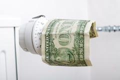 Element och en dollar Pengar på uppvärmningbatteriet royaltyfri bild