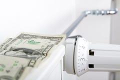 Element och en dollar Pengar på uppvärmningbatteriet arkivfoto