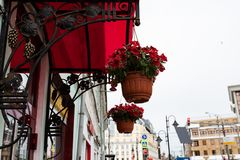 Element of urban landscape. Wrought-iron bronze canopy pattern over the door, bright red roof and flowers in hanging pots royalty free stock photography
