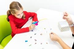 Elementair Leeftijdsmeisje die in de Zitting van de Kind Beroepstherapie Speelse Oefeningen met Haar mening van TherapeutTop doen royalty-vrije stock afbeelding