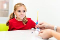 Elementair Leeftijdsmeisje die in de Zitting van de Kind Beroepstherapie Speelse Oefeningen met Haar Therapeut doen royalty-vrije stock afbeeldingen