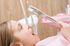Elementair leeftijdsmeisje die haar tanden in de spiegel in pediatrische tandkliniek bekijken royalty-vrije stock afbeelding