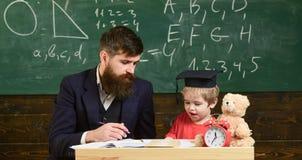 Elementair onderwijs De vader onderwijst zoon, bespreekt, verklaart Het concept van het onderwijs Jong geitje die met leraar best stock foto