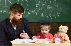 Elementair onderwijs Jong geitje die met leraar bestuderen De vader onderwijst zoon, bespreekt, verklaart Het concept van het ond royalty-vrije stock foto's