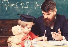 Elementair onderwijs Leraar in formele slijtage en leerling in baret in klaslokaal, bord op achtergrond kid royalty-vrije stock fotografie