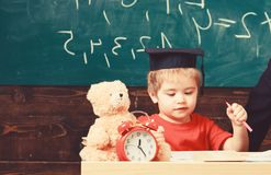 Elementair onderwijsconcept Eerste eerstgenoemde met stuk speelgoed op bureau Leerling in baret, bord op achtergrond Jongen op be stock afbeelding