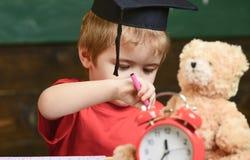 Elementair onderwijsconcept Eerste eerstgenoemde met stuk speelgoed op bureau, sluit omhoog Leerling in baret, bord op achtergron stock afbeeldingen