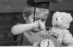 Elementair onderwijsconcept Eerste eerstgenoemde met stuk speelgoed op bureau, sluit omhoog Leerling in baret, bord op achtergron royalty-vrije stock afbeelding