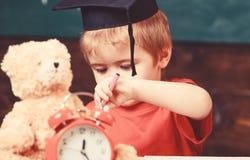 Elementair onderwijsconcept Eerste eerstgenoemde met stuk speelgoed op bureau, sluit omhoog Leerling in baret, bord op achtergron stock afbeelding
