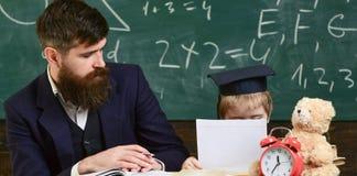 Elementair onderwijsconcept Jong geitjestudies met leraar, die met aandacht luisteren De vader onderwijst elementaire zoon royalty-vrije stock foto's