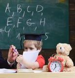 Elementair onderwijsconcept Leerling in baret, bord op achtergrond Jong geitjestudies met voorbeeldenboek, mannelijke hand royalty-vrije stock foto
