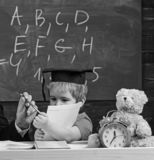Elementair onderwijsconcept Leerling in baret, bord op achtergrond Jong geitjestudies met voorbeeldenboek, mannelijke hand stock foto