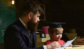 Elementair onderwijsconcept Leraar en leerling in baret, bord op achtergrond De vader onderwijst elementaire zoon stock afbeeldingen