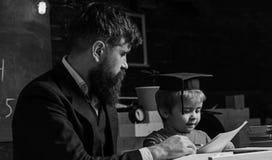 Elementair onderwijsconcept Leraar en leerling in baret, bord op achtergrond De vader onderwijst elementaire zoon royalty-vrije stock foto's