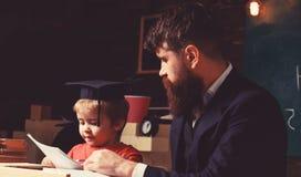 Elementair onderwijsconcept Leraar en leerling in baret, bord op achtergrond De vader onderwijst elementaire zoon stock fotografie