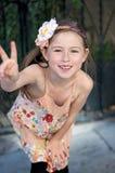 Elementair oud meisje die bij camera glimlachen, die een vredesteken met haar vingers maken Stock Afbeelding