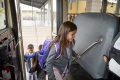 Elementair schoolmeisje die op de schoolbus krijgen naar huis te gaan royalty-vrije stock foto's