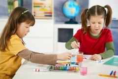 Elementaire leeftijdskinderen die in klaslokaal schilderen Royalty-vrije Stock Foto's