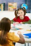 Elementaire leeftijdskinderen die in klaslokaal schilderen Stock Foto's