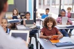 Elementaire studenten die leraar, over schoudermening bekijken royalty-vrije stock foto's