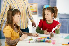 Elementary age children painting in classroom. Elementary age children sitting around desk enjoying painting with colors in art class at primary school classroom Royalty Free Stock Photo