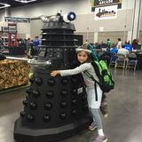 Young costumed girl hugs BBC Dalek character. Elementary age costumed girl hugs Dalek at Wizard World in Portland, OREGON Stock Images