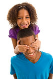 Elementary age girl covering teenage boys eyes Royalty Free Stock Photos